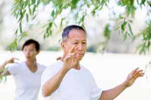 Older couple practicing tai-chi in the park to help with osteoporosis.